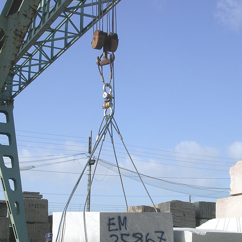 A heavy stone block is lifted with a crane