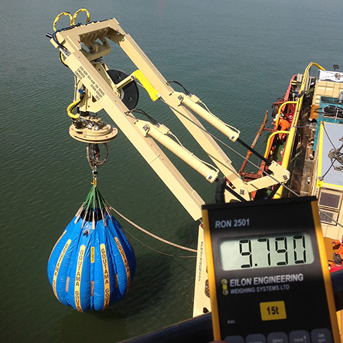 A water bag is suspended above the water from ships crane