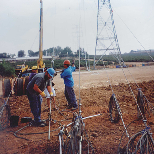 Workers install anchors for guy wires