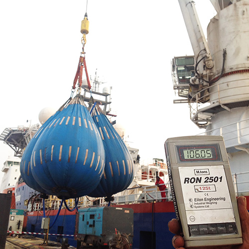 Three water bags are suspended from ship's crane